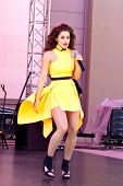 Girl in yellow dress singing a catchy song