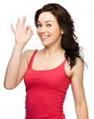 Young woman dressed in red is showing OK sign, isolated over white