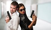 stock photo of gunfights  - Young Couple Holding Gun against an abstract background - JPG