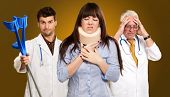 foto of neck brace  - Woman With Neck Brace In Front Of Doctors On Brown Background - JPG