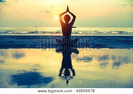Yoga woman sitting in lotus pose on the beach during sunset, with reflection in water (cross-process poster