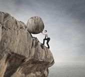 stock photo of dangerous situation  - fatigued businessman supports large boulder - JPG