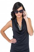Serious elegant brunette wearing sunglasses on the phone on white background
