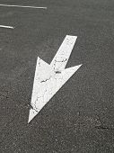 arrow sign on the parking lot pavement