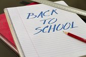 back to school written in notebook with pencil and slat