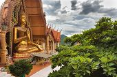 Wat tham khao noi buddhist temple under a cloudy sky in rainy season, Kanchanaburi province in Thailand