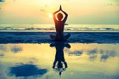 stock photo of reflection  - Yoga woman sitting in lotus pose on the beach during sunset - JPG