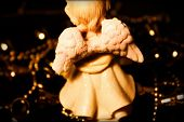 stock photo of cherubim  - figure little  angel from back  with golden bells - JPG