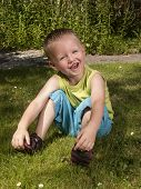 Toddler Is Laughing On The Grass In The Garden