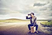 stock photo of binoculars  - young man looks with binoculars sitting on a suitcase in the middle of a deserted road - JPG