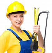 Young happy lady as a construction worker with hacksaw and tape measure, isolated over white