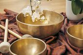 stock photo of buddhist  - An image of some singing bowls and a white orchid - JPG