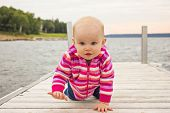 Little girl crawling on the dock