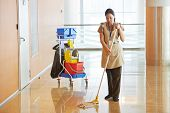 stock photo of broom  - Female cleaner maid woman worker with mop in uniform cleaning corridor pass or hall floor of business building - JPG