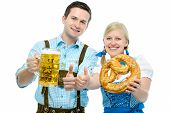 stock photo of stein  - Couple in traditional bavarian tracht holding Oktoberfest beer steins and pretzel - JPG