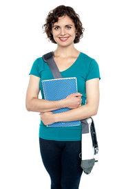 foto of sling bag  - Trendy woman wearing trendy sling bag across and clutching notebook - JPG