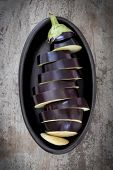 Sliced eggplant or aubergine in black dish.  Overhead view, over old timber.
