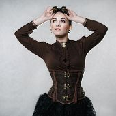 image of mimicry  - Beautiful fashionable woman in the style of steampunk on a gray background - JPG