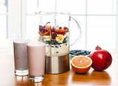 stock photo of banana  - Prepared smoothies and healthy smoothie ingredients in blender with fresh fruit ready to blend on kitchen table - JPG