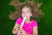 Blond kid children girl playing flute lying on grass backyard lawn