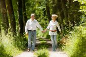 Mature or senior couple running, deeply in love having a walk holding each other tight in late spring or early summer