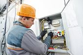 pic of fuse-box  - Young adult electrician builder engineer screwing equipment in fuse box - JPG