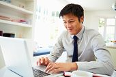 Asian Businessman Working From Home On Laptop