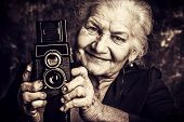 Portrait of a beautiful old lady with her old camera. Vintage, retro style.