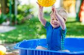 stock photo of kiddie  - Little toddler boy having fun with splashing water and playing ball in summer garden pool - JPG