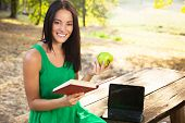 Beautiful Young WomanHolding Book And Apple
