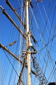 image of mast  - Closeup of sailing ship mast against blue sky - JPG