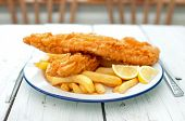 image of plate fish food  - Two pieces of battered fish on a plate with chips