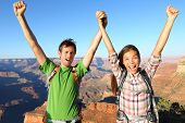 Happy people celebrating cheering in Grand Canyon. Young multiethnic couple on hiking travel excited
