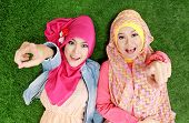 picture of muslimah  - Portrait of close up two beautiful happy muslim woman lying on grass - JPG