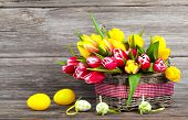 Spring Tulips In Wooden Basket With Easter Eggs, On Wooden Background