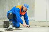 foto of overhauling  - Two industrial tiler builder worker installing floor tile at repair renovation work - JPG