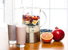 stock photo of blender  - Prepared smoothies and healthy smoothie ingredients in blender with fresh fruit ready to blend on kitchen table - JPG