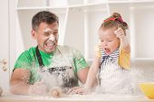 pic of apron  - Funny portrait of cute little daughter with handsome father cooking pastry - JPG