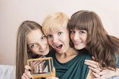 Three Young Caucasian Girls With Teeth Brackets Sitting Together And Smiling. Holding Present In Hom