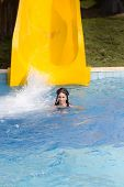 stock photo of toboggan  - Young girl swimming in pool in water park with toboggan in background - JPG