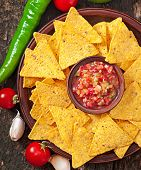 foto of nachos  - Mexican nacho chips and salsa dip in bowl on wooden background - JPG