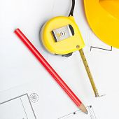 Yellow Construction Helmet With Pencil And Measure Tape Above Blueprint