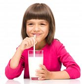 Cute little girl drinks milk using drinking straw, isolated over white