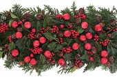 Christmas red bauble decoration with winter greenery over white background.