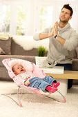 stock photo of crying  - Young father praying for peace by crying baby - JPG