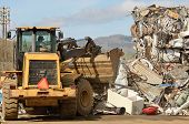 stock photo of scrap-iron  - Wheel loader being used to pile scrap metal at a metal recycling plant - JPG