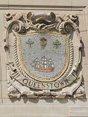 Mosaic shield of renowned port city Queenstown at the facade of United States Lines