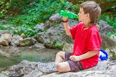 young happy smiling child boy drinking water on forest river background
