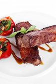 fresh red beef meat steak barbecue garnished vegetable salad and basil  in half of pepper bell on wh
