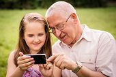 Grandchild shows grandfather smartphone